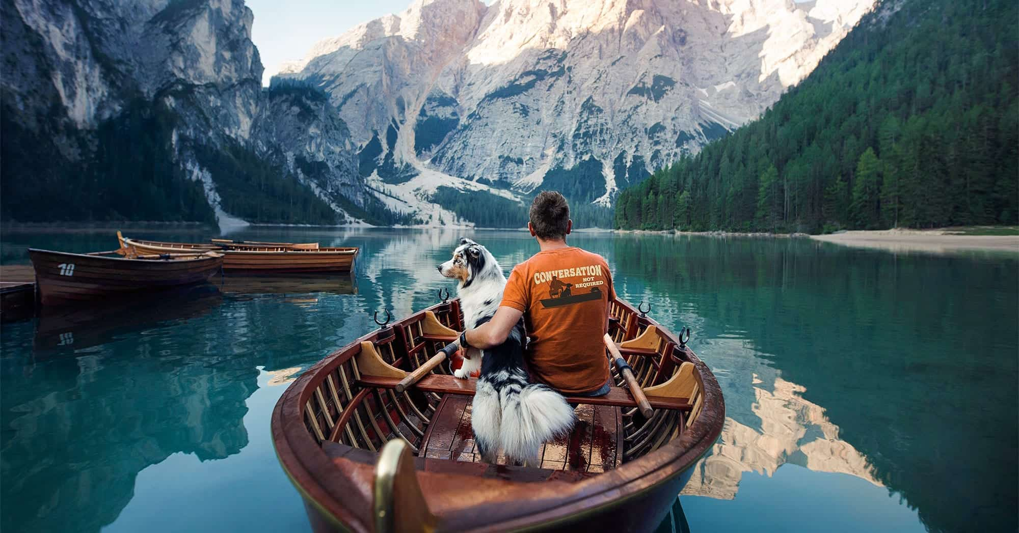 man with dog on lake
